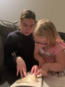 A blind woman in a blue sweater sitting on a couch with a young girl in a pink dress on her lap. They are sharing a print/Braille book.