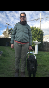 Shauna and her guide dog, Barney, with green grass and trees in the background. Shauna is wearing rose gold coloured sunglasses that have a clear amber tint to the lenses, khaki green cargo pants, brown leather ankle boots, and a hooded green puffer winter jacket with a dark grey turtleneck showing underneath. Barney, a male black Labrador retriever, is wearing a black gentle leader, Guide Dogs for the Blind harness, and a black collar with a brown leather leash.