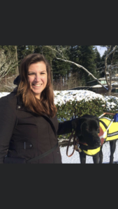 A photo of Shauna and guide dog, Abner, taken at the guide dogs for the blind Oregon campus, in Boring, Oregon in December 2016. It is a close-up photo of Shauna and Abner with snow in the background. Shauna has long brown hair, and is smiling, and is wearing a black winter jacket. Abner is wearing his bright yellow and black raincoat, GDB harness, collar and leash. Abner is a black Labrador retriever, and in this photo he is two years old.