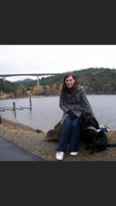 A photo of Shauna and Rafferty. Shauna is wearing a dark plaid jacket, dark blue jeans, and white running shoes, and has long brown hair. Rafferty is a black lab retriever and is wearing his GDB harness, collar and leash. They are seated on a large rock at lake Coeur d'Alene in Idaho. There is a beautiful landscape behind them of the lake, and a bridge off in the far distance.