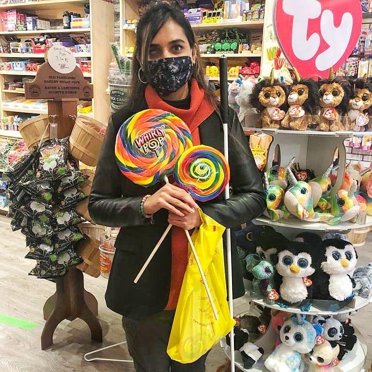 This photo shows Wajiha standing in a candy shop holding two huge lollipops across each other in her hands. The bigger lollipop is about 12 inches across and the smaller one is about 8 inches across. She's looking at the camera, smiling and wearing a black face mask with tiny flowers patterned on it. She's wearing a trendy pink cashmere sweater and a black blazer over it, that has leather sleeves while the rest of the fabric looks like cotton, with medium gray jogger pants and black flip-flops. Her waist length brown and blonde straight hair is down with a silky white and black knotted headband on top of her head with side bangs framing her face. Her long white cane is resting on the left side of her body and a shopping bag with a few candies is hanging from her wrist. There are different kinds of candies on the shelf on her right and some stuffed toys to her left. The photo was taken in in landscape mode.